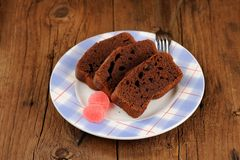 Pieces of homemade chocolate cake with pink candies  Royalty Free Stock Photo
