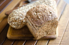 Pieces of homemade wholemeal bread. Over wooden table with clean table napkin Stock Photography