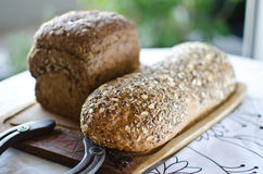 Pieces of homemade wholemeal bread. Over wooden table with clean table napkin Royalty Free Stock Images