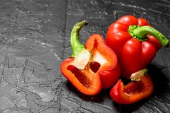 Pieces of and a host sweet pepper. On black rustic background stock photos