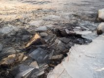 Pieces of ice floes on shore stones by a freezing lake. Pieces of ice floes on shore stones by a freezing Nordic lake Stock Photo
