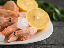 Pieces of ice from the frozen shrimp in a clay bowl on a dark wooden table. Frozen shrimp with lemon and herbs on cutting Board on wooden table. Diet seafood Royalty Free Stock Photography