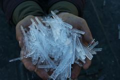 Pieces of ice in hands stock photography