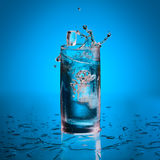 Pieces of ice throwed in glass with water. Glass of water standing on wet surface and few pieces of ice dropped with splashes and bubbles stock image