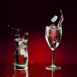 Pieces of ice throwed in two glasses. Two clear glasses of water standing on wet surface and few pieces of ice dropped with splashes and bubbles stock photography