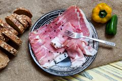 Pieces of Italian prosciutto on a plate. Sliced slices of Italian prosciutto, bread and peppers on a plate close-up on a wooden table Stock Photos