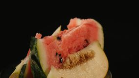 Pieces of juicy ripe watermelon and melon on plate rotating on black background stock footage
