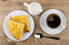 Pieces of khachapuri, jug of milk, spoon and coffee. Pieces of khachapuri in plate, jug of milk, spoon and coffee on wooden table. Top view Stock Image