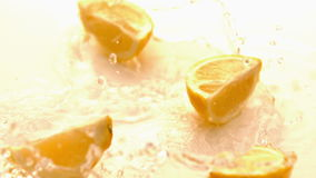 Pieces of lemon falling on white wet surface stock video