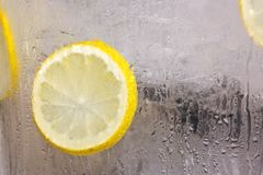 Pieces of lemon in ice glass Royalty Free Stock Photo