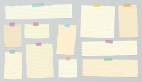 Pieces of light brown ruled torn note paper with colorful adhesive, sticky tape. Royalty Free Stock Photography