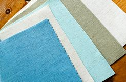 Pieces of linen sample. Five colors of linen fabrics sample in wooden table Royalty Free Stock Photography