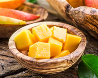 Pieces of mango fruit in a wooden bowl. Stock Photo