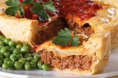 Pieces of meat pie and a garnish of green peas. Horizontal macro Royalty Free Stock Images