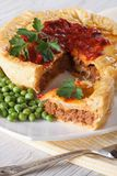 Pieces of meat pie and a garnish of green peas. Vertical Stock Photography
