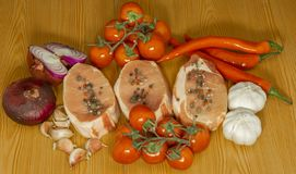 Pieces of meat surrounded by vegetables and spices. stock images