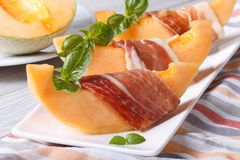 Pieces of melon wrapped in ham Horizontal close-up Royalty Free Stock Photo