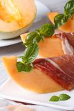 Pieces of melon wrapped in ham vertical close-up. Pieces of melon wrapped in ham with basil on a white plate on the table. vertical close up Stock Image