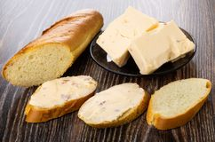 Pieces of melted cheese with bacon in plate, bread, sandwiches with cheese on table stock photo