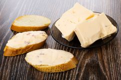 Pieces of melted cheese with bacon in plate and sandwiches with cheese on table royalty free stock images
