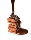 On pieces of milk chocolate pours dark chocolate. On a white background Royalty Free Stock Photo