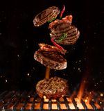 Pieces of minced meal for hamburgers flying above grill Royalty Free Stock Photos