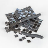 Pieces of mosaic tile with nipper. In white background Royalty Free Stock Photography