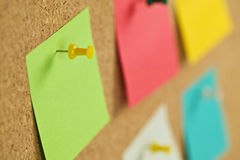 Pieces of note paper on a cork bulletin board Royalty Free Stock Photos
