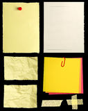 Pieces of notepaper. Pieces of yellow notepaper isolated on black background stock images