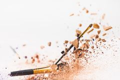 Pieces Of Cosmetic Powder With Makeup Brushes Falling Stock Image