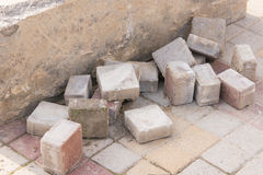Pieces of old paving slabs lie in concrete block on the pavement Stock Image