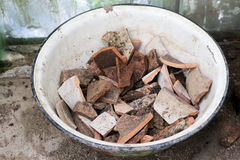 Pieces oof a brown clay pot in a bowl. Pieces oof a brown clay pot in a bow Royalty Free Stock Photo