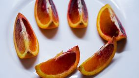 Pieces of blood orange on white plate, top view royalty free stock images