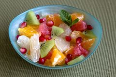 A small blue bowl with multicolored fruits. Pieces of Orange, grapefruit, mandarin, pomelos, kiwi, and grains of pomegranate, decorated with mint leaves Stock Image