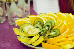 Pieces of orange, kiwi and banana lie on a plate. royalty free stock images
