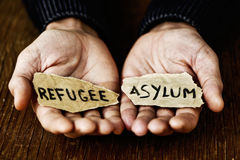 Pieces of paper with words refugee and asylum Stock Images