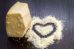 Pieces of parmigiano reggiano or parmesan cheese on black wood b Royalty Free Stock Photography
