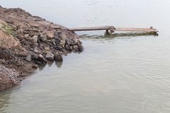 Pieces of paved road on the water with a bridge. Royalty Free Stock Photo