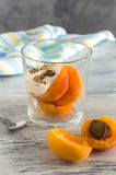 Pieces of peach with cream and nuts with a glass. Peach with a stone in the open form on the table. royalty free stock photos