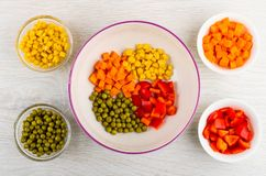 Pieces of pepper, carrot, green peas, corn in ceramic bowl and glass bowls with ingredients on table. Top view stock images