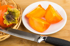 Pieces of persimmons in saucer and knife on table Stock Photography