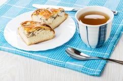 Pieces of pie with chicken, knife, tea, teaspoon on napkin Stock Photos