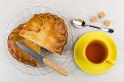 Pieces of pie in dish, knife, tea, teaspoon and sugar. Pieces of pie with stuffed in transparent dish, knife, cup of tea, teaspoon and sugar cubes on wooden Royalty Free Stock Photography