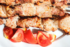 Pieces of pieces of red tomato and shish kebabs Stock Photos