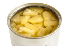 Pieces of pineapple in a tin on white. Royalty Free Stock Photos