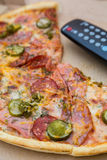 Pieces pizza in box with tv remote control. Pieces pizza with sausages and bacon in pasteboard box with tv remote control Royalty Free Stock Photography