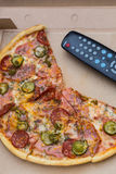 Pieces pizza in box with tv remote control. Pieces pizza with sausages and bacon in pasteboard box with tv remote control Royalty Free Stock Photo