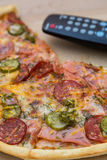 Pieces pizza in box with tv remote control. Pieces pizza with sausages and bacon in pasteboard box with tv remote control Royalty Free Stock Images