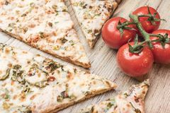 Pieces of pizza and cherry tomatoes on a branch on a light wooden background royalty free stock image