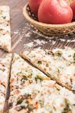 Pieces of pizza close-up and fresh tomatoes on a brown wooden background Royalty Free Stock Photo